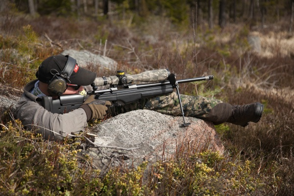 Skytt skjuter liggandes med vapnet på benet.